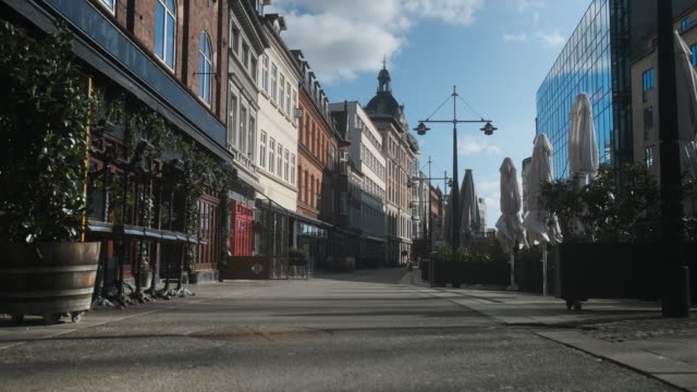 Closed Stalls and Restaurants and an Empty Street in Denmark A steady clip of a quiet and peaceful street in Aarhus, Denmark in the midst of the covid-19 pandemic; folded table umbrellas, and closed restaurants surrounding the street. denmark stock videos & royalty-free footage