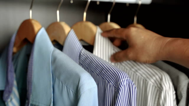 closed up, A businessman chooses shirt in your wardrobe before you go to work or before a night out. closed up, A businessman chooses shirt in your wardrobe before you go to work or before a night out. button down shirt stock videos & royalty-free footage