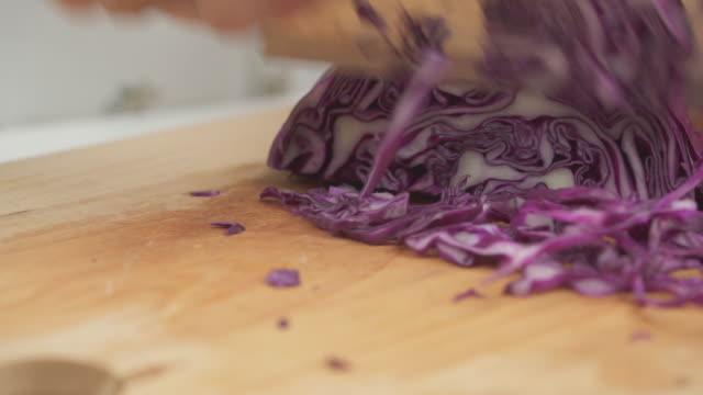 Closed up hand Chopped Purple cabbage on table Closed up hand Chopped Purple cabbage on table cabbage stock videos & royalty-free footage