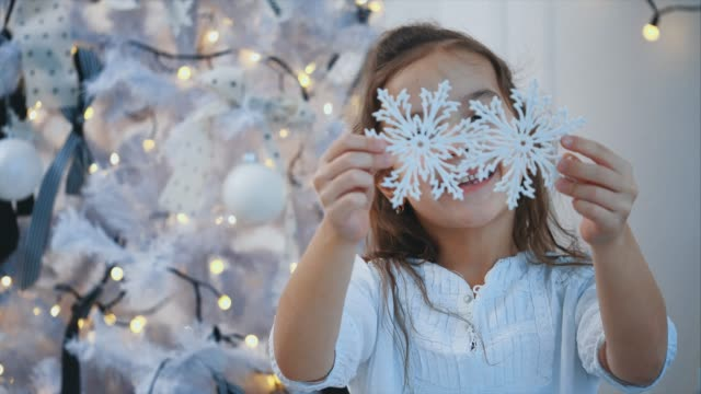 Close-up 4k video where smiling girl, little snow princess, near christmas tree, on a white background, extends two faux snowflakes to the camera.