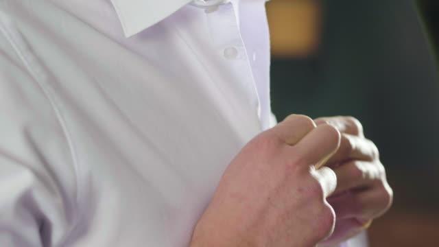 クローズアップ 彼のロフトのハンサムな男はセクシーな方法で彼のセクシーな白いシャツをドレスアップし、彼の部屋を見て、確かな自分自身を見て笑顔。 - 着る点の映像素材/bロール