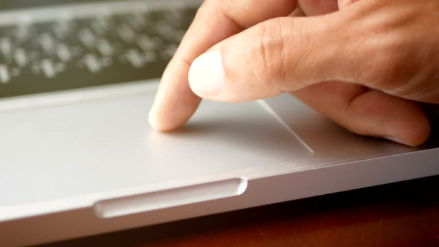 4k. close-up a man working with notebook laptop, using finger with keyboard and touchpad or trackpad for slide and zoom in, zoom out. - touchpad video stock e b–roll