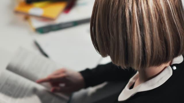 yakın çekim a kız öğrenci veya öğrenci kitap okuma. ödevini yapıyor - çalışma kitabı stok videoları ve detay görüntü çekimi