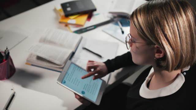 yakın çekim a kız öğrenci veya öğrenci bir tablet kullanır, ölçekler ve linkler aracılığı ile gider. ödevini yapıyor - çalışma kitabı stok videoları ve detay görüntü çekimi