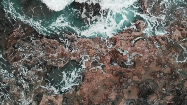 Close-up aerial view of big sea waves hitting on rocks at stormy weather creating white foam. Cyprus Paphos Close-up aerial view of big sea waves hitting on rocks at stormy weather creating white foam. Cyprus Paphos coastal feature stock videos & royalty-free footage