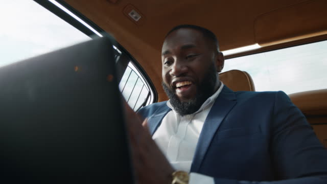 Closeup african businessman clapping hands at car. Man talking video call at car