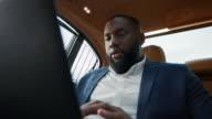 istock Closeup afro man working laptop at car. Businessman chatting on computer. 1219315911