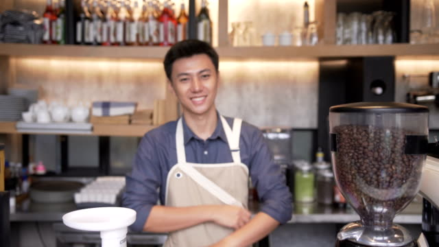 foco e close-up vista frontal: Young Asian barista homem está sorrindo para ser dono de café café - vídeo