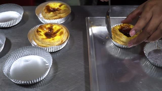 yakın çekim ve izleme atış yapma ve pişirme yumurta tart yanı sıra alüminyum folyo mutfakta koyarak şef el - muhallebi stok videoları ve detay görüntü çekimi