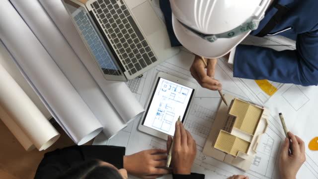 建設現場で青写真について議論する、建築家とエンジニアのクローズアップ - 図面点の映像素材/bロール