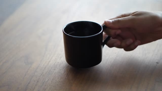 vídeos de stock e filmes b-roll de a closeup as a woman's hand picks up a hot steaming cup of tea or coffee from a dining room walnut colored wood table with sunlight coming from a window beyond. - caneca