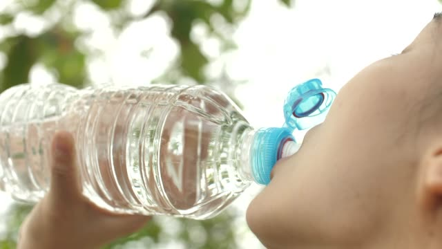 Close-up Asian Fitness Woman drinking Water after Running