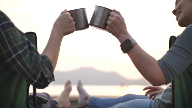 Close-up Asian Woman clinking cups together in Camping