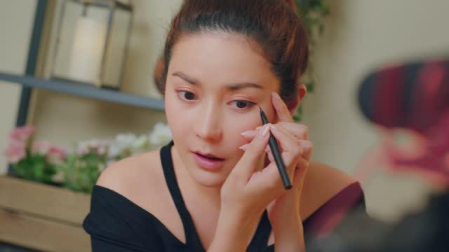 stockvideo's en b-roll-footage met close-up: aziatische vrouw make-up influencer opname make-up tip met behulp van eyeliner tutorial virale inhoud - eyeliner