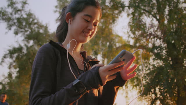 Close-up Attractive Asian Teenager girl listening music while Walking and running in the public park. Young woman jogging exercising while using smart phone in the morning.