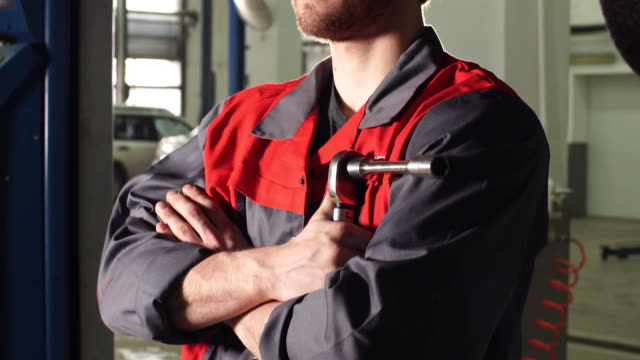 Close-up auto mechanic crossed hands and looking at camera while standing under lifting car in repair garage video