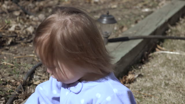 Closeup baby blonde brown hair blowing in wind playing rocks. video
