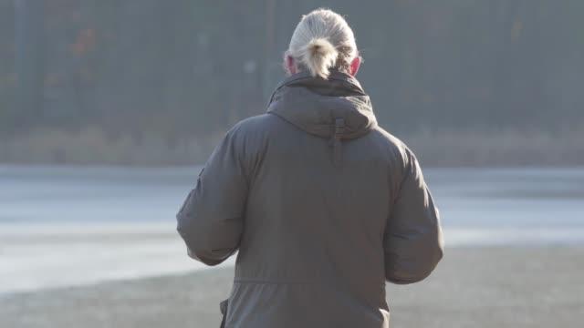 stockvideo's en b-roll-footage met close-up weergave van volwassen kaukasische man staande op lake shore en rond te kijken. eenzame mannelijke toerist genieten van zonnige herfst dag buitenshuis. vrije tijd, levensstijl, reizen. - paardenstaart haar naar achteren