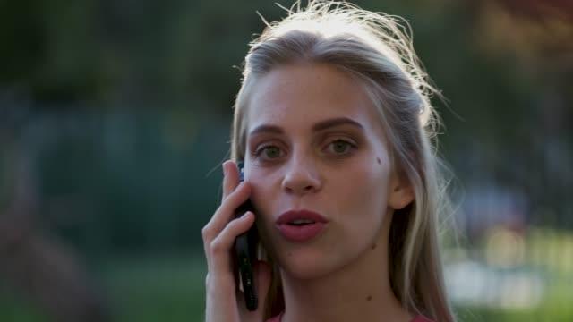vidéos et rushes de portrait rétro-éclairé 4k d'une très belle jeune adolescente parlant sur un mobile et regardant dans la caméra - 18 19 ans