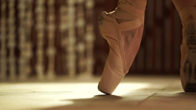 nahaufnahme ballerina bindet ihre ballett pantoffeln auf - ballettschuh stock-videos und b-roll-filmmaterial