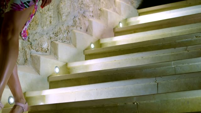 close-up, beautiful female long legs in sandals, going down the marble, white steps with backlight video