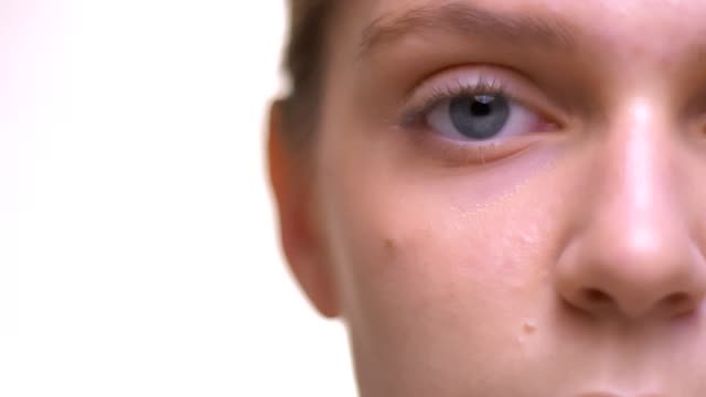 Close-up beautiful healthy skin focused on eye and lips of healthy caucasian female and white background Close-up beautiful healthy skin focused on eye and lips of healthy caucasian female and white background. sideways glance stock videos & royalty-free footage