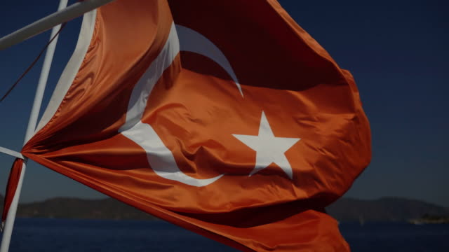 close-up - beautiful red flag of turkey flying in the wind on a sunny summer day - полумесяц форма предмета стоковые видео и кадры b-roll