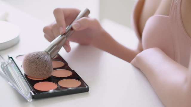 vídeos de stock e filmes b-roll de closeup beauty young asian woman applying makeup with brush cheek on face, beautiful girl using blusher with palette make-up on facial, skin care and cosmetic table fashion concept. - rímel