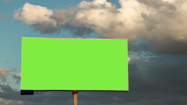 Close-up billboard with empty green screen on moving clouds in the sky background in time lapse
