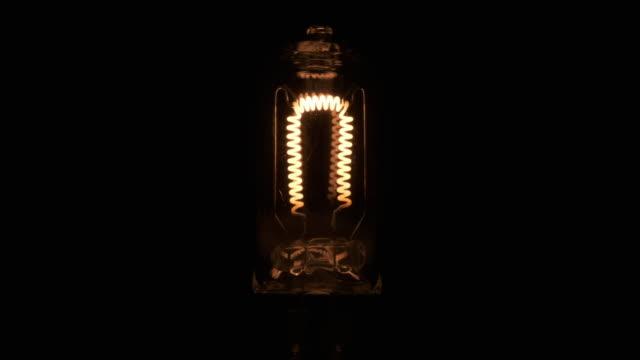 Plan rapproché, spirale clignotante d'une lampe incandescente. Filament de tungstène de scintillement. - Vidéo