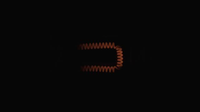 Close-up, blinking spiral of an incandescent lamp. Flicker tungsten filament.