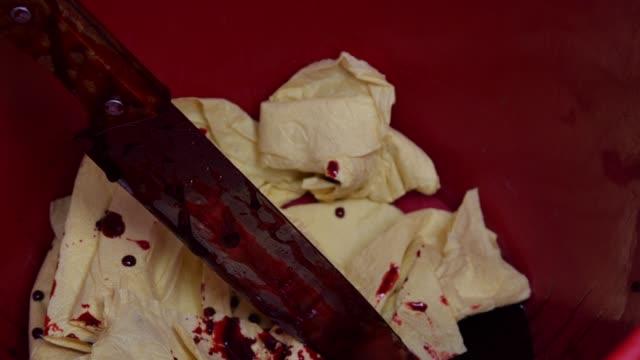 Close-up bloody knife in a bin
