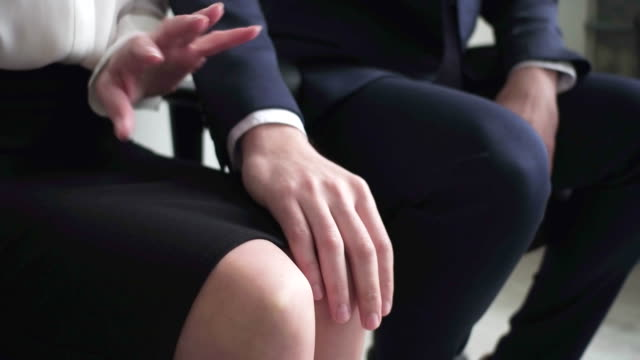 close-up boss hand touching woman's knee - minacce video stock e b–roll