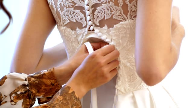 close-up, bride fees. the bride is dressed for the wedding. bridesmaid laces up white lace dress with ribbon. wedding dress details, close up - wedding fashion stock videos and b-roll footage