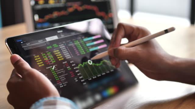 geschäftsmann analysiert börsendaten auf digitalen tablets - überprüfung stock-videos und b-roll-filmmaterial
