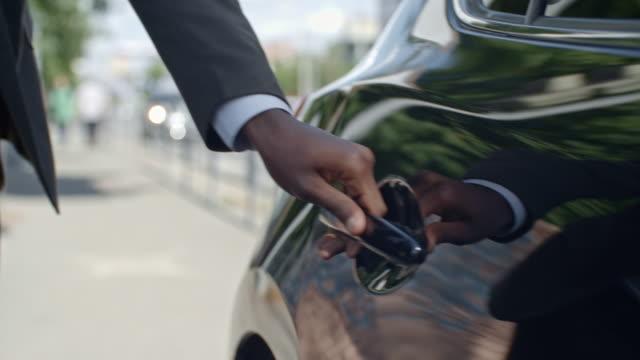 closeup businessman getting into car - pasażer filmów i materiałów b-roll