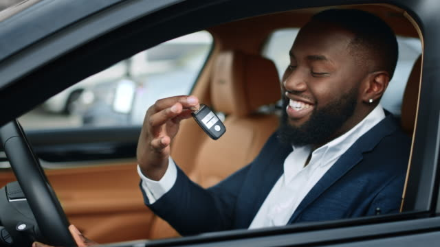 Closeup businessman shaking key in new car. African man smiling in vehicle