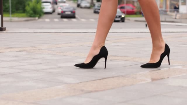 close-up businesswomans feet in heels walking down pavement in city to work - scarpe video stock e b–roll