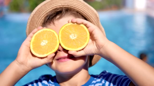 close-up carefree travel cute boy posing with half of orange on eyes at sea beach background - cappello video stock e b–roll