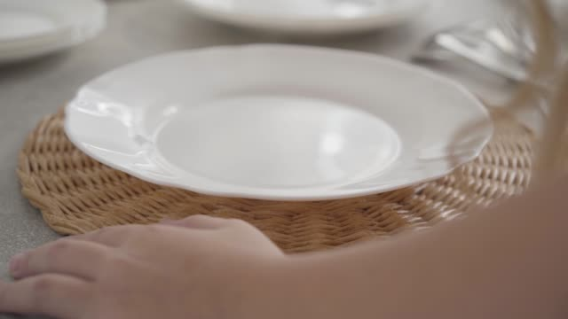 Close-up Caucasian female hands serving plates at the table. Diligent teen placing dishware at plate coasters. Close-up Caucasian female hands serving plates at the table. Diligent teen placing dishware at plate coasters. positioning stock videos & royalty-free footage