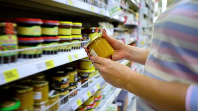 vídeos de stock e filmes b-roll de closeup caucasian woman hands near shop shelves choosing light honey in grocery market - mel