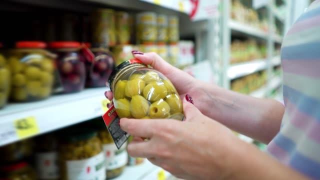 Closeup kaukasischen Frau Hände in der Nähe von Regalen Wahl Marinade grüne Oliven im Lebensmittelmarkt – Video