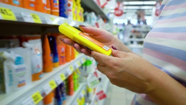 closeup caucasian woman near shop shelves choosing cosmetics in market - sun cream stock videos & royalty-free footage