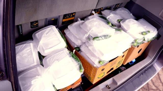 クローズアップ、プラスチック弁当箱と段ボール容器のチャリティーミールが車に積み込まれます。covid19のロックダウン中に貧しい人々のための無料の食糧配達。援助の寄付 - community activism点の映像素材/bロール