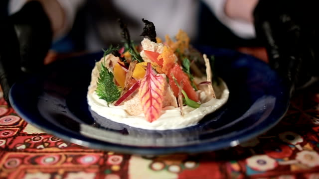 Closeup chef in white uniform presenting delicious vegetable salad. Slow motion video