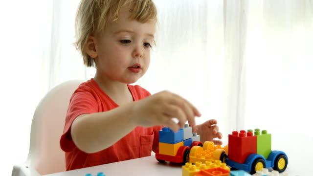 vídeos de stock e filmes b-roll de closeup childs hands play colorful plastic bricks - obras em casa janelas