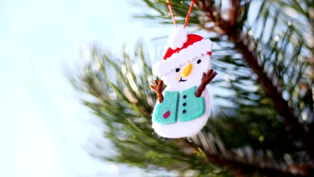 close-up, Christmas toys hanging on a snow-covered Christmas tree branch. winter, frosty, snowy, sunny day