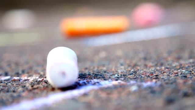 nahaufnahme, farbige buntstifte liegen auf dem bürgersteig - kreide weiss stock-videos und b-roll-filmmaterial