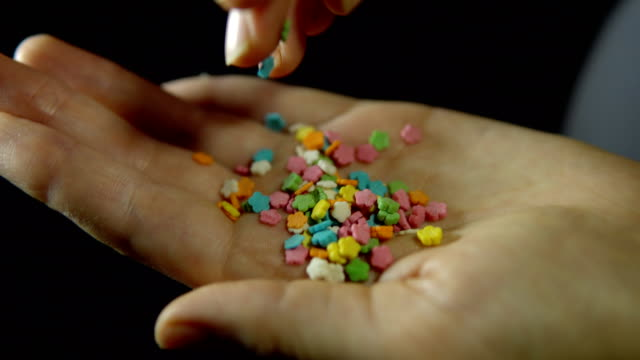 Close-up confectionery powder in a human hand on a black background. Close-up of a human hand, fingering a handful of confectionery powder in the form of a flower in the palm of a hand against a black background, unrecognizable person. handful stock videos & royalty-free footage