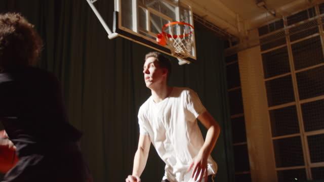 vidéos et rushes de confrontation rapprochée entre deux joueurs de basket-ball sport endurance attaque de la salle de jeu de sport de nuit - ligue sportive